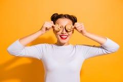 Het portret van leuke charmante aantrekkelijke dame die rond het sluiten voor de gek houden verbergend haar ogen met koekjes prob stock fotografie