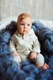 Het portret van leuke het meisjeszitting van de 8 maand oude baby op het bed op grote maat breide deken Royalty-vrije Stock Fotografie