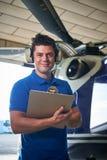 Het portret van Mannelijke Aero-Ingenieur With Clipboard Carrying controleert uit stock foto's