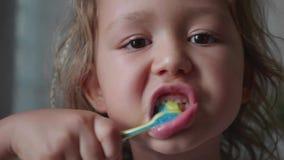 Het portret van meisje borstelt intensief haar tanden in badkamers stock video