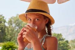 Het portret van meisje is drinkig vers sap, de zomerberg landsc Royalty-vrije Stock Foto's