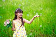 Het portret van meisje geniet van met zeepbels op groene weide Royalty-vrije Stock Afbeelding