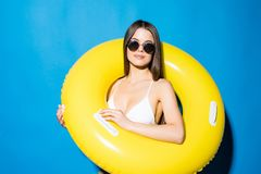 Het portret van meisje kleedde zich in zwempak en zonnebril binnen opblaasbare die ring en het bekijken camera over blauwe achter stock afbeelding