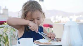 Het portret van meisje snijdt een pannekoek en eet het voor ontbijt stock videobeelden