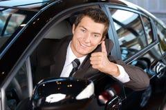 Het portret van mensenzitting in het nieuwe auto tonen beduimelt omhoog Royalty-vrije Stock Fotografie