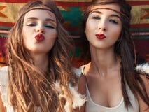 Het portret van Modieuze hippiemeisjes die pret hebben en verzendt kus over e Stock Foto's