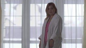 Het portret van mollig meisje in witte badjas en roze nachtjapon draait en onderzoekt scherp de camera die bevinden zich voor stock footage