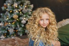 Het portret van mooi blondemeisje zit en glimlacht op een bed in Kerstmistijd stock afbeelding