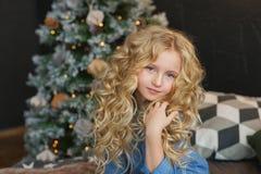 Het portret van mooi blondemeisje zit en raakt haar haar op een bed in Kerstmistijd stock afbeelding