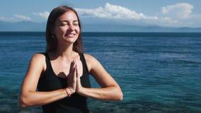 Het portret van mooi glimlachend meisje mediteert met gesloten ogen, oceaan op achtergrond stock footage