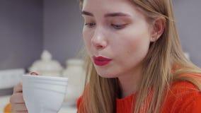 Het portret van mooi Kaukasisch meisje in rode sweater drinkt koffie stock video