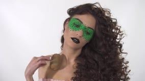 Het portret van mooi krullend meisje met creatief maakt omhoog het leiden van rijpe kiwi langs de overzichten van gezicht en lich stock footage