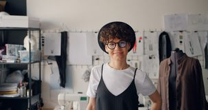 Het portret van mooi meisje kleedt ontwerper het glimlachen zich bevindt in alleen workshop stock videobeelden