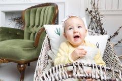 Het portret van mooi meisje zit thuis op een stoel dichtbij een open haard in Kerstmis royalty-vrije stock fotografie