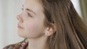 Het portret van mooi tienermeisje die haar hoofd zodat haar schudden fladdert en kijkt in camera het glimlachen Gezicht van stock video