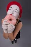 Het portret van mooi wijfje bootst het eten van een smakelijk roze na Stock Afbeeldingen