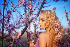 Het portret van mooie blondevrouw in het bloeien nam tuin, de Zonnige dag van de de lentestemming toe royalty-vrije stock afbeeldingen