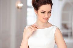 Het portret van mooie donkerbruine bruid met elegant kapsel en de make-up die lang luxehuwelijk dragen kleden zich Royalty-vrije Stock Foto