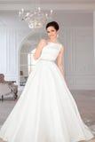 Het portret van mooie donkerbruine bruid met elegant kapsel en de make-up die lang luxehuwelijk dragen kleden zich Stock Foto