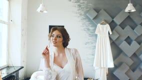 Het portret van mooie jonge bruid die en in cameravrouw stellen glimlachen stelt aan fotograaf stock footage