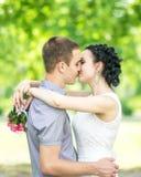Het portret van mooie jonge paar vrouwelijke bruid met klein huwelijksroze bloeit rozenboeket en het mannelijke bruidegom kussen  royalty-vrije stock afbeeldingen