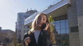Het portret van mooie jonge vrouw loopt op de stadsstraat terwijl het spreken met haar vriend op smartphone vrij stock footage