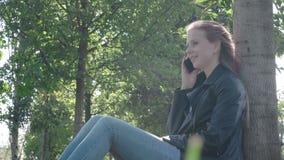 Het portret van mooie jonge vrouw loopt op de straat van de stad terwijl ze met haar vriend op de smartphone praat Behoorlijk stock footage