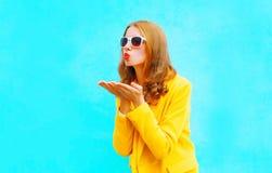 Het portret van mooie jonge vrouw verzendt een luchtkus in gele laag stock afbeeldingen