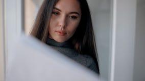 Het portret van mooie onderneemster werkt met documenten die zich in heldere ruimte bevinden stock footage