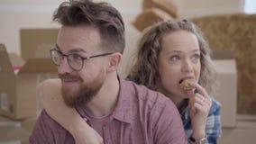 Het portret van mooie vrouw eet koekje, dicht omhoog koesterend van achter de gebaarde mens in glazen De uitgepakte dozen zijn in stock videobeelden