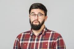 Het portret van ongelukkig bepaald Europees mannetje met ernstig en ongerust gemaakt kijkt tegen grijze achtergrond royalty-vrije stock fotografie