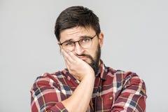 Het portret van ongelukkig bepaald Europees mannetje met ernstig en ongerust gemaakt kijkt tegen grijze achtergrond stock fotografie