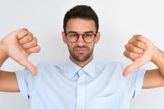 Het portret van ongelukkig mannetje draagt om in glazen, gestreept overhemd die de camera met negatieve uitdrukking bekijken, die royalty-vrije stock foto