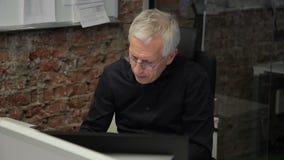 Het portret van oude professor die de studententests in zijn bureau met glas en bakstenen muren controleert stock footage