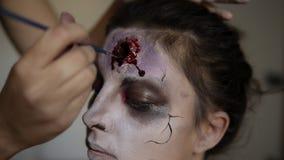 Het portret van het proces van de zombiesamenstelling, ziet dicht omhoog onder ogen, bloedige wonden op gezicht Professionele kun stock video