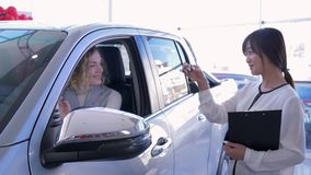 Het portret van professionele autoverkoper overhandigt de cliënt van de sleutelsvrouw binnen voertuig terwijl het kopen van auto  stock video