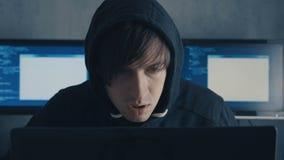 Het portret van IT professionele hakkerprogrammeur in kap die aan computer in het centrum van de cyberveiligheid werken vulde met stock footage