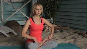 Het portret van rijpe blonde vrouw, die in lotusbloem zit stelt buiten tijdens meditatie stock video