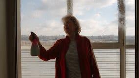 Het portret van rijpe vrouw bespuit vensterreinigingsmachine binnen op groot venster - Front View stock video