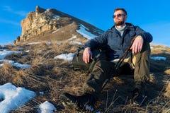 Het portret van rustige Hipster-reiziger met baard in zonnebril zit op aard Stock Fotografie