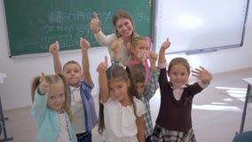 Het portret van schooljonge geitjes met leraar die duimen tonen en juicht dan in klaslokaal op achtergrond van raad toe op school stock videobeelden
