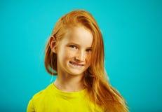 Het portret van schuw kindmeisje, drukt verlegenheid uit, draagt gele t-shirt, heeft mooie rode haar en sproeten, portret royalty-vrije stock foto's