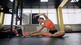 Het portret van sportieve geschikte gelukkige mooie jonge vrouw die in sportkleding, doen Gedraaid Hoofd aan Knie stelt uitwerken stock video