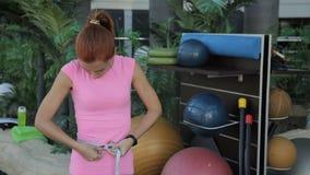 Het portret van sportvrouw die haar taille door de band in de luxegymnastiek meet stock footage