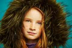 Het portret van het studioclose-up van leuk redheaded kindmeisje met sproeten verborg in groot kapjasje stock afbeelding