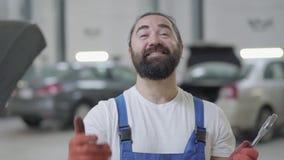 Het portret van succesvolle werktuigkundige maakt het uitnodigen gebaren en glimlacht holding reusachtige moersleutel in handen G stock footage