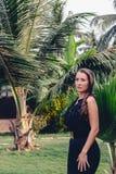 Het portret van a suntanned meisje tegen een tropisch bos backgroun Royalty-vrije Stock Foto's