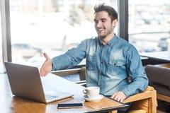 Het portret van tevreden gelukkige jonge zakenman in jeansoverhemd zit in koffie en begroet een arbeider door een webcam en royalty-vrije stock fotografie