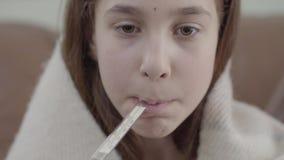 Het portret van tiener in een deken wordt verpakt neemt een thermometer in haar mond en meet de temperatuur die Het meisje stock videobeelden