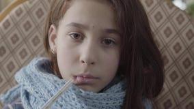 Het portret van tiener verpakte in warme sjaal houdend een thermometer in haar mond en meet de temperatuur Het meisje stock video